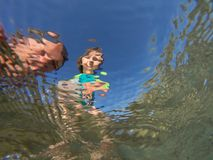 Underwater view of a father and her daughter with distorted face. Father and her toddler daughter having fun at the sea. Distorted faces view through water Royalty Free Stock Image