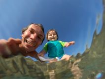 Underwater view of a father and her daughter with distorted face. Father and her toddler daughter having fun at the sea. Distorted faces view through water Stock Photos