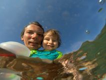 Underwater view of a father and her daughter with distorted face. Father and her toddler daughter having fun at the sea. Distorted faces view through water Stock Images