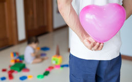 Father hiding a pink heart balloon behind his back, excited to surprise his daughter for her birthday royalty free stock photo