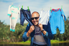 Father hiding between son's clothes Royalty Free Stock Photos