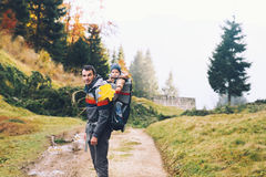 Father hiking with child on nature in autumn forest. Royalty Free Stock Photography