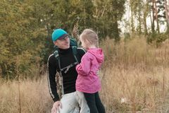 Father hiking with kid on backpack stock photos