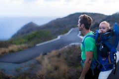 A father hiking on a trail with his kid. Sceanic ocean view. Staying fit. Healthy lifestyle royalty free stock image