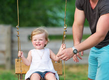 Father with his adorable baby daughter playing swing in the garden. royalty free stock image