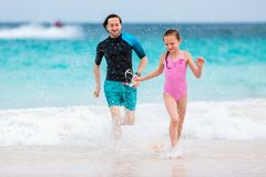 Father and daughter at beach. Father and his adorable daughter at beach having fun together stock photo