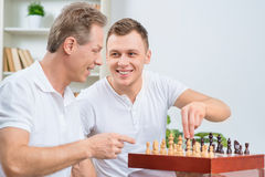 Father and his adult son playing chess. Adapt grand masters. Pleasant handsome positive adult son holding chessman while playing chess with his father royalty free stock photography