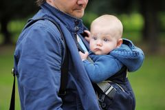 Father and his baby in a baby carrier. Father and his baby boy in a baby carrier outdoors Royalty Free Stock Photography