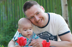 A father, his baby boy in arms and tulips Royalty Free Stock Photo