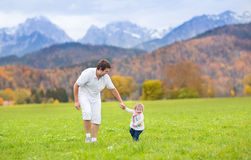 Father with his baby daughter in field in mountains Stock Images
