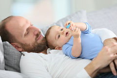 Father and his baby relaxing on a sofa Royalty Free Stock Image