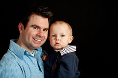 Father and his baby son on black Stock Photography