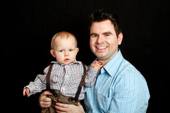 Father and his baby son on black Stock Image