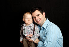 Father and his baby son on black Stock Photos