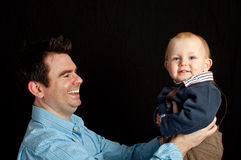 Father and his baby son on black Stock Photo