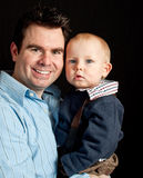 Father and his baby son on black Royalty Free Stock Image