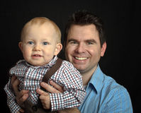 Father with his baby son on black backdrop Stock Images
