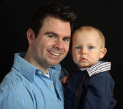 Father with his baby son on black backdrop Royalty Free Stock Photo