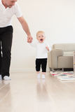 Father and his beautiful baby girl playing and learning how to walk. Stock Photography