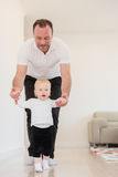 Father and his beautiful baby girl playing and learning how to walk. Royalty Free Stock Image