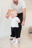 Father and his beautiful baby girl playing and learning how to walk. Royalty Free Stock Photos