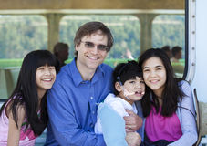 Father with his biracial children, holding disabled son on ferry. Boat deck. Boy has cerebral palsy royalty free stock image