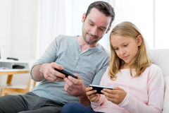Father and his blond daughter using mobile Royalty Free Stock Photos