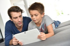 Father and his boy child playing together on tablet Stock Photos