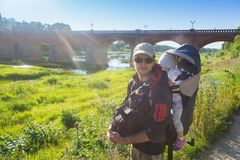 Father with his child in a backpack traveling and hiking in summer evening royalty free stock image