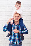 Father with his child on his neck isolated over white brick back Royalty Free Stock Image