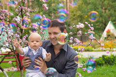 Father and his child playing with soap bubbles. A dad and his son playing soap bubbles in the park Stock Image