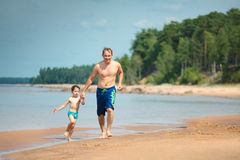 Father and his child running along the beach Royalty Free Stock Photo