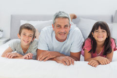 Father with his children lying on bed Royalty Free Stock Photo