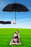 Father and his children lying on grass under umbrella Stock Images