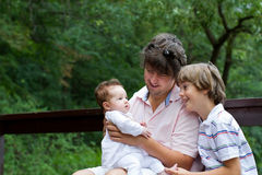 Father with his children in a park. Father with son and newborn daughter in a park Stock Photography