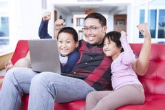 Father and his children playing games on laptop Royalty Free Stock Photos