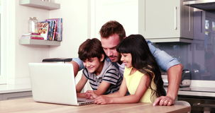 Father and his children using laptop. At home stock video
