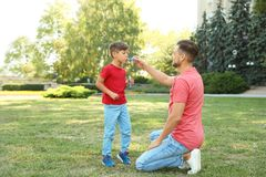 Father and his cute child playing with soap bubbles. In green park on sunny day. Happy family Royalty Free Stock Images