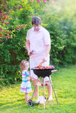 Father and his cute daughter grilling in the garden Stock Image