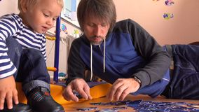 Father and his cute little kid assembling puzzle together. Father and his small boy having spare time at home. 4K video stock video