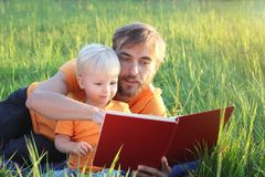 Father and his cute toddler son read book together in nature. Authentic lifestyle image. Parenting concept.  stock photography