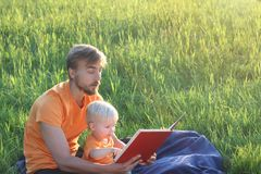 Father and his cute toddler son read book together outdoor. Authentic lifestyle image. Copy space.  Royalty Free Stock Photo