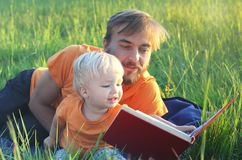 Father and his cute toddler son read book together outdoor. Authentic lifestyle image. Parenting or childhood concept.  Royalty Free Stock Photos