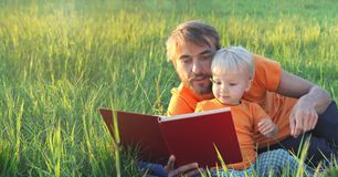 Father and his cute toddler son read book together in summer field. Authentic lifestyle image. Parenting concept. Copy space.  Stock Image