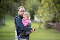 Father with his daughter in baby carrier. Green nature. Royalty Free Stock Photography