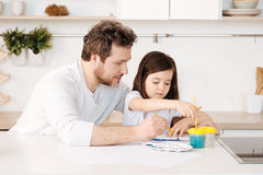Father and his daughter engaged in the painting process royalty free stock photos