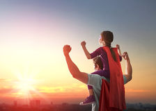 Father and his daughter. Happy loving family. Father and his daughter child girl playing outdoors. Daddy and his child girl in an Superhero's costumes. Concept Royalty Free Stock Images