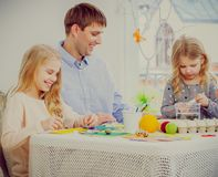 Father and his daughter painting and decorating easter eggs.family having fun and enjoying flavored tea and cupcakes. Cheerful father and his daughters painting Stock Photo