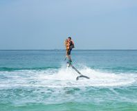 Father and his daughter posing at new flyboard at Caribbean tropical beach. Positive human emotions, feelings, joy. Funny cute chi. Ld making vacations and Royalty Free Stock Photos