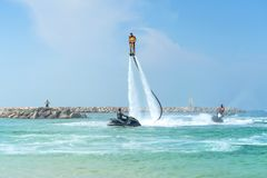 Father and his daughter posing at new flyboard at Caribbean tropical beach. Positive human emotions, feelings, joy. Funny cute chi. Ld making vacations and Stock Images
